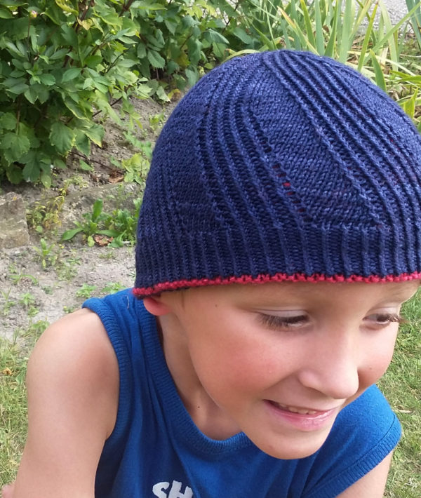 Display of the twisted stitches side of the reversible Winter in August hat, a knitting pattern designed by Julie Partie