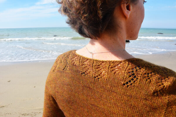 Zoom on the back of the Melaine cardigan designed by Julie Partie, knitting pattern for a 3/4 sleeves cropped cardigan with sleeves panels