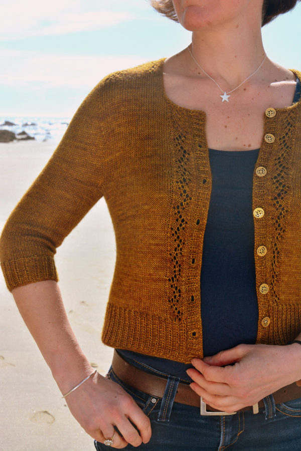 Zoom on the front of the Melaine cardigan designed by Julie Partie, knitting pattern for a 3/4 sleeves cropped cardigan with sleeves panels
