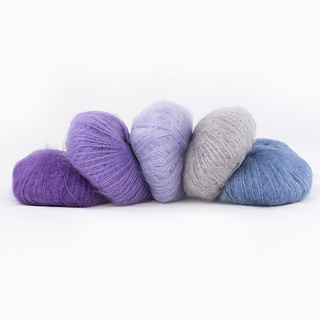 Five balls of Silky Kid by Kremke Soul Wool in shades going from bright purple to jeans blue