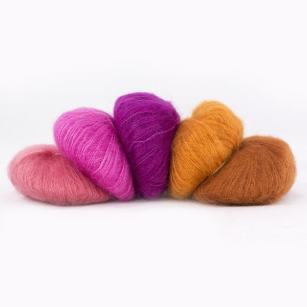Five balls of Silky Kid by Kremke Soul Wool in shades going from coral pink to mahogany brown