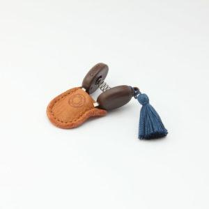 Présentation de mini-ciseaux Seki de la marque Cohana avec pompon bleu dans leur étui en cuir
