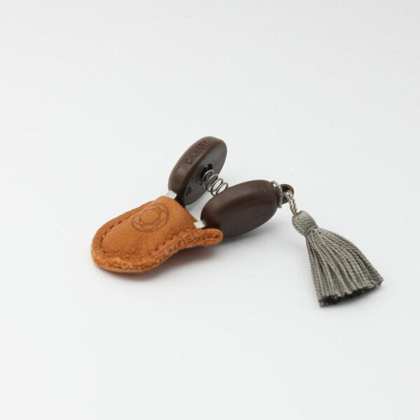Présentation de mini-ciseaux Seki de la marque Cohana avec pompon gris dans leur étui en cuir
