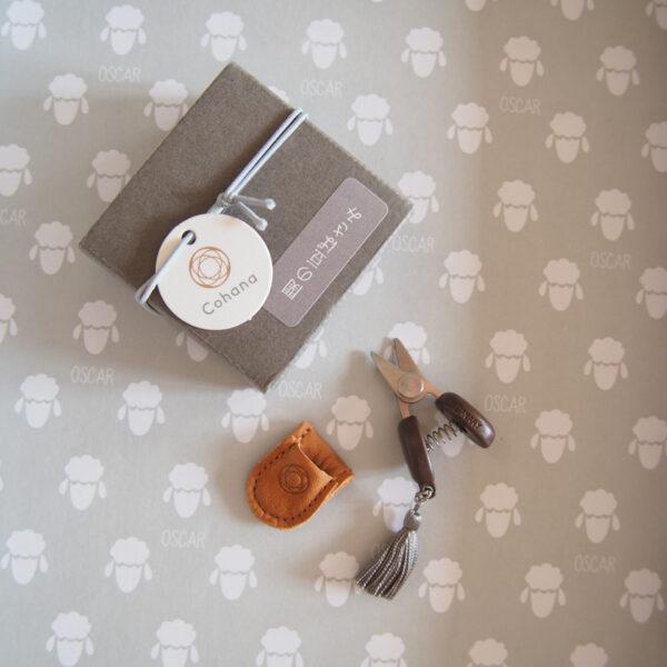 Présentation de mini-ciseaux Seki de la marque Cohana avec pompon gris près de leur étui en cuir et de leur boîte d'emballage