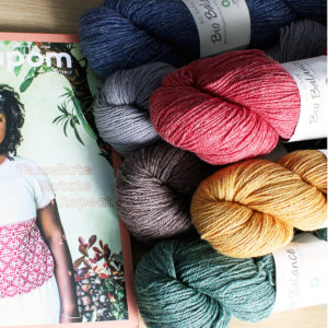 6 skeins of Bio Balance by BC Garn, in different colorways, sitting next to a Pompom Quarterly magazine