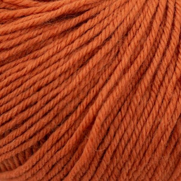 Zoom on a ball of Kremke Soul Wool's Bébé Soft Wash in the Brûlis colorway (burnt orange)