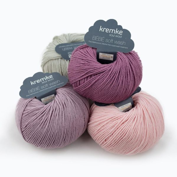 Four balls of Kremke Soul Wool's Bébé Soft Wash in heather, light purple, baby pink and light grey