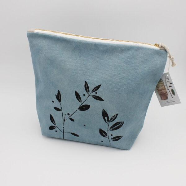 Display of a big zippered pouch, handcrafted by Kaliko, made of blue plant dyed organic cotton and raw linen, with a vegetal stamped pattern