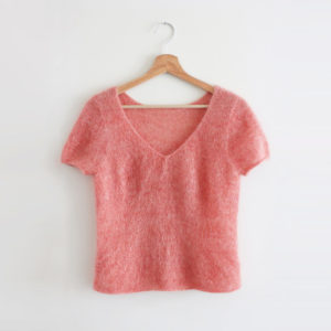 Display of a Red Blush top designed by Julie Partie, to be knitted with 2 strands of mohair and silk lace weight yarn