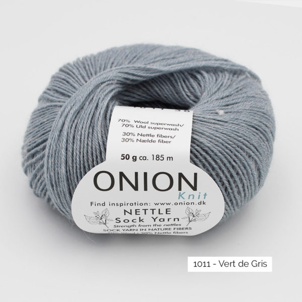 A ball of Onion's Nettle Sock Yarn d'Onion in the Vert de Gris colorway (greyish sage green)