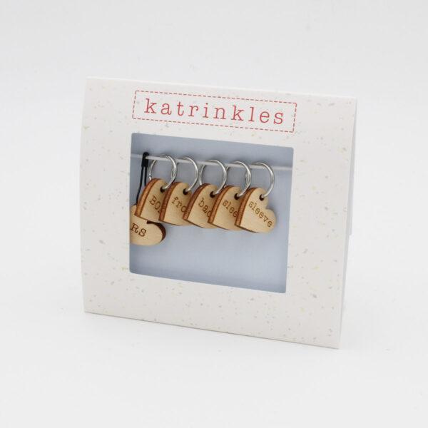 Présentation d'un set d'anneaux marqueurs avec pendants en bois en forme de coeur gravés de la marque Katrinkles