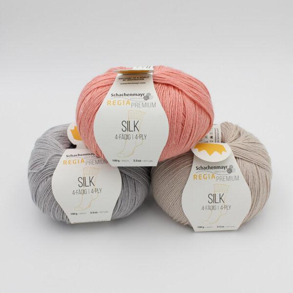 Trois pelotes de Regia Premium Silk dans des coloris assortis (gris clair, camel et abricot)