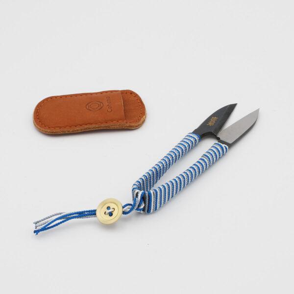 Présentation d'un coupe-fil Shozaburo pour Cohana, avec manche habillé de soie bleue, grise et blanche, posé à côté de son étui en cuir gravé