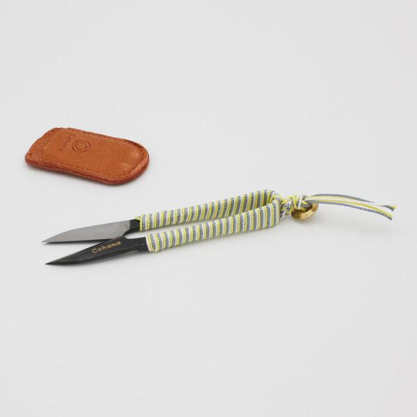 Présentation d'un coupe-fil Shozaburo pour Cohana, avec manche habillé de soie jaune, grise et blanche, posé à côté de son étui en cuir gravé