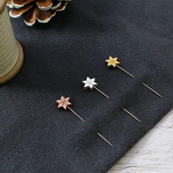 Présentation d'un jeu de trois épingles longues Cohana à tête en bois marqueté en forme d'étoile de noël