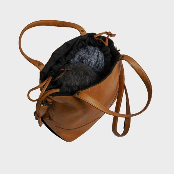 Display of a Lofoten shoulder strap project bag by Muud, in the whisky colorway, open