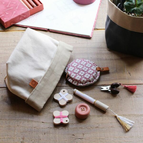 Display of Cohana's small notions pouch made of waxed canvas, in the natural and beige colorway, presented with notions on the side for scale