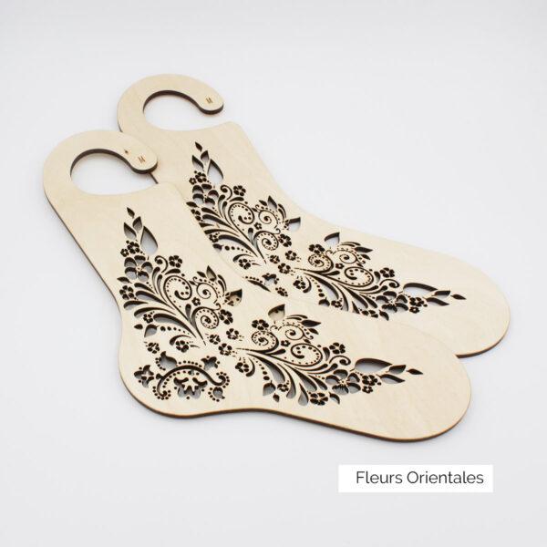 Présentation d'une paire de bloqueurs de chaussettes en bois à motif gravé de fleurs stylisées