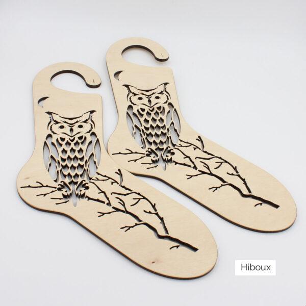 Présentation d'une paire de bloqueurs de chaussettes en bois à motif gravé de hiboux