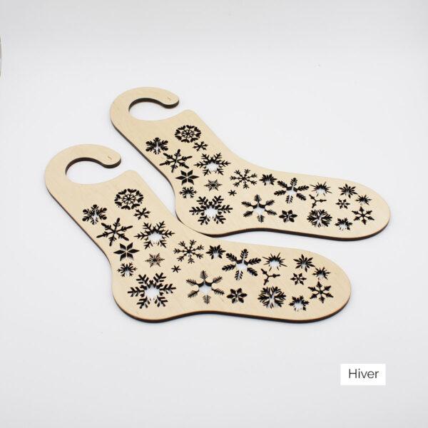 Une paire de bloqueurs de chaussettes en bois à motifs de flocons