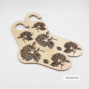Présentation d'une paire de bloqueurs de chaussettes en bois à motif gravé de fleurs d'hortensias