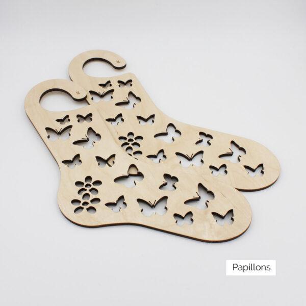 Présentation d'une paire de bloqueurs de chaussettes en bois à motif gravé de papillons