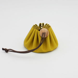 Bourse en cuir jaune fermée par un lien marron et un bouton en bois de la marque Cohana