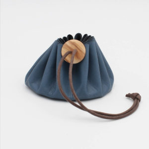 Cohana's blue Himeji leather purse closed by a brown wax cotton link and a wooden button