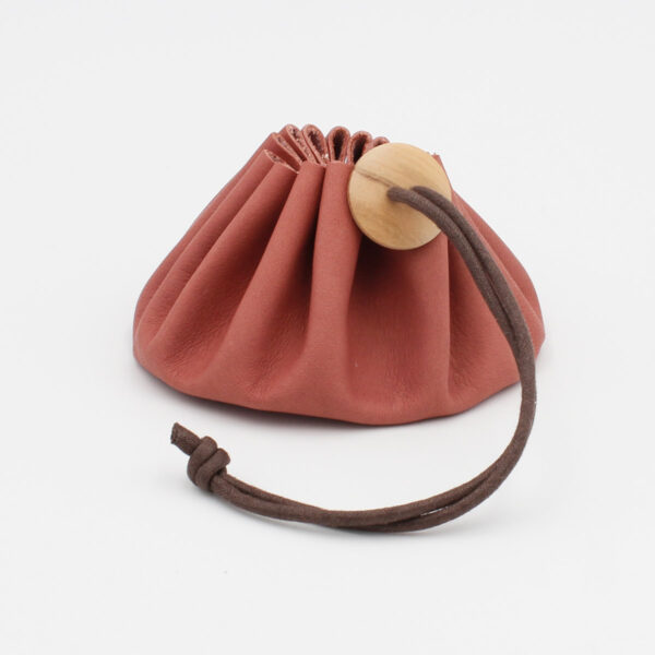 Cohana's pink Himeji leather purse, closed by a brown wax cotton link and a wooden button