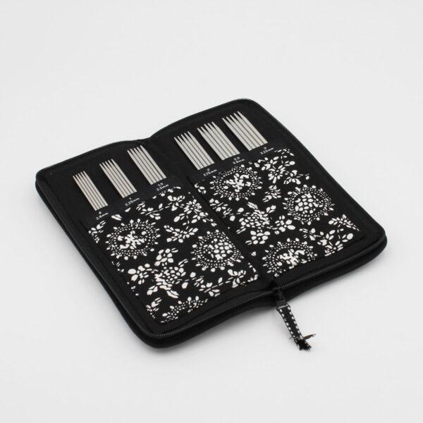 Pochette noire et blanche du kit d'aiguilles double pointe ChiaoGoo en métal, ouverte, les aiguilles sont rangées dans leur compartiment numéroté