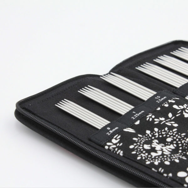 Zippered black and white case, open, containing a set of Chiaogoo double pointed steel needles