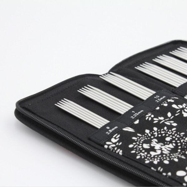 Gros plan sur l'intérieur de la pochette noire et blanche du kit d'aiguilles double pointe ChiaoGoo en métal, les aiguilles sont rangées dans leur compartiment numéroté