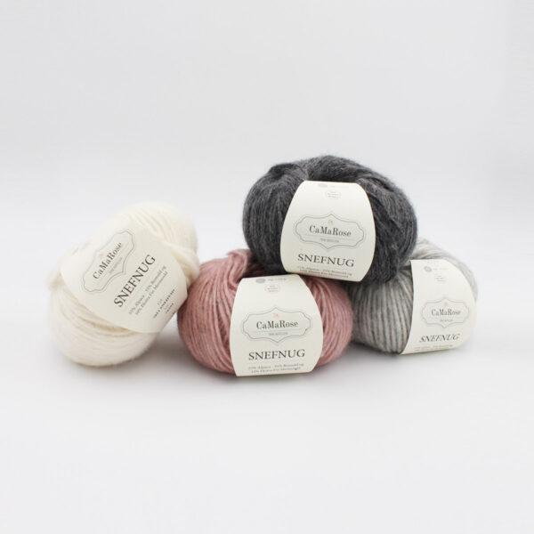 Quatre pelotes de Snefnug de CaMaRose, dans les coloris blanc, gris clair, gris foncé et rose