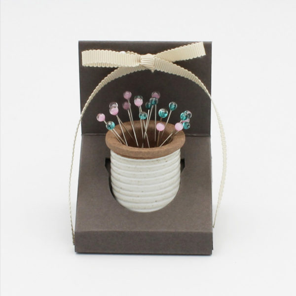 Cohana's magnetic ceramic pin holder, shaped as a spool, with blue and pink glass head pins in its packaging