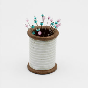 Cohana's magnetic ceramic pin holder, shaped as a spool, with blue and pink glass head pins