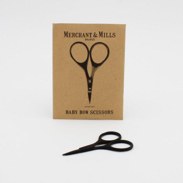 Ciseaux Baby Bow de Merchant & Mills, noirs, présentés à côté de leur pochette cartonnée kraft logotypée noir