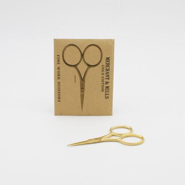 Petits ciseaux Merchant & Mills édition spéciale dorés présentés à côté de leur pochette cartonnée