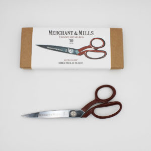 "Merchant & Mills Red Extra Sharp Tailor Shears, 25cm (10"") long, with a red handle, displayed next to their cardboard box"