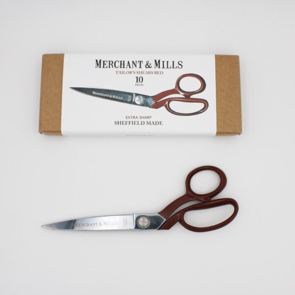 """Merchant & Mills Red Extra Sharp Tailor Shears, 25cm (10"""") long, with a red handle, displayed next to their cardboard box"""