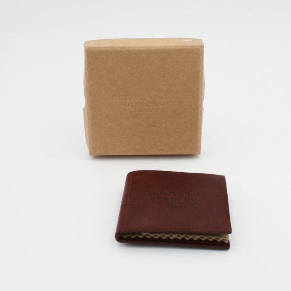 Dark rusty brown leather needle wallet, engraved with the brand name, closed and displayed next to its cardboard kraft box