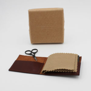 Dark rusty brown leather needle wallet with inside pockets and two inside suede sheets to pin your needles. Displayed with a pair of baby bows scissors and its cardboard box.
