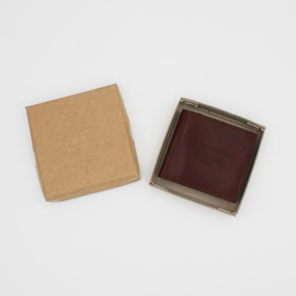 Dark rusty brown leather needle wallet, engraved with Merchant & Mills name, closed, displayed inside its cardboard kraft box