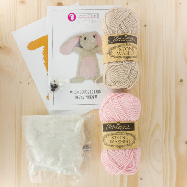 Display of a Hardicraft softie knitting kit, to knit Doutze Rabbit, with its leaflet, 2 balls of Scheepjes yarn and filling