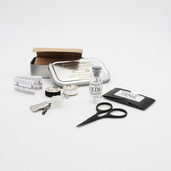 Présentation du contenu du kit SOS (rapid repair kit) de Merchant & Mills avec mètre ruban, aiguilles, ciseaux, fil et pochette d'épingles, à côté de leur boîte