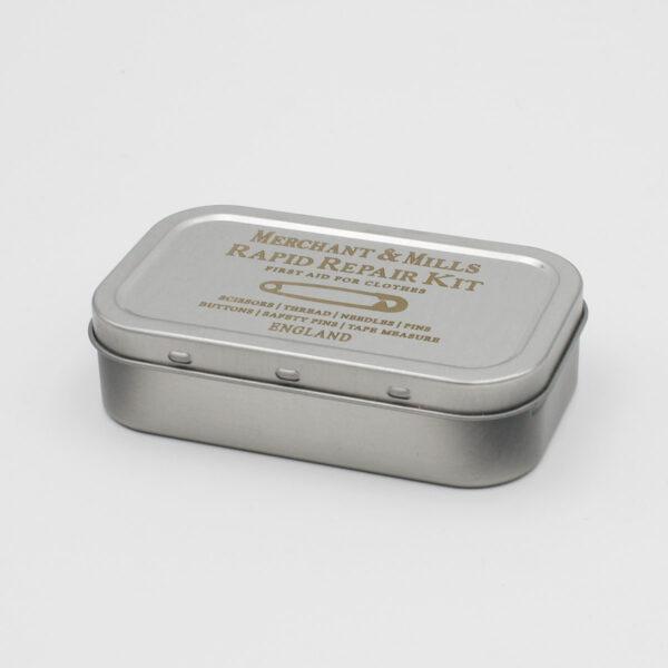 Boîte du kit SOS (rapid repair kit) de Merchant & Mills, en métal brossé imprimé avec le nom de la marque, du produit et son contenu