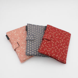 Display of the three types of fabric pouches made to keep the Kinki Amibari interchangeable needles sets organized, one in a red fabric with white dragonflies, one in a dark blue fabric with Japanese stars and one in soft pink with flowers