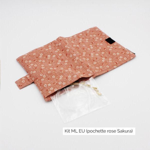 Présentation de la pochette du kit Seeknit de Kinki Amibari en taille ML-EU, en tissu rose doux fleuri de blanc et rouge (sakura), ouverte à plat avec câbles dépassant sur le côté