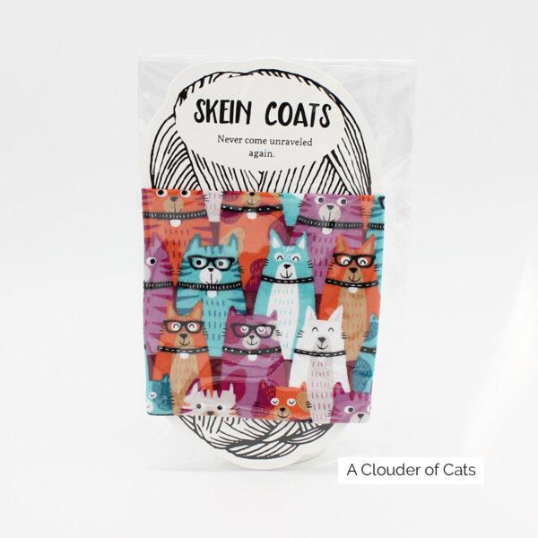 """Présentation du Skein Coat à motif chats dans les tons orange, bleu, prune et rose """"A Clouder of Cats"""" de Precious Knits dans son emballage"""