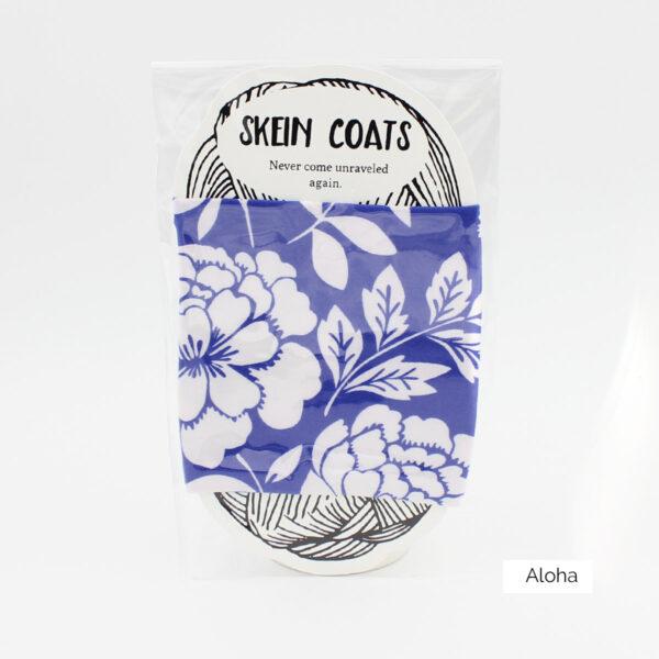"Présentation du Skein Coat ""Aloha"" de Precious Knits, à motif fleuri type hawaïen blanc sur fond uni bleu"