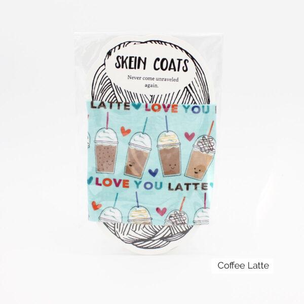 """Présentation du Skein Coat """"Coffee Latte"""" de Precious Knits à motifs de to-go cups de café sur fond bleu clair"""